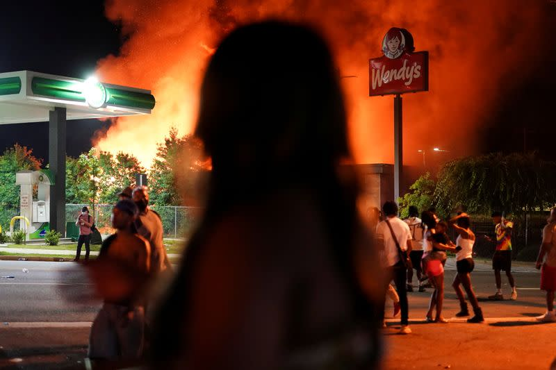 People watch as a Wendy's burns following a rally against racial inequality and the police shooting death of Rayshard Brooks, in Atlanta