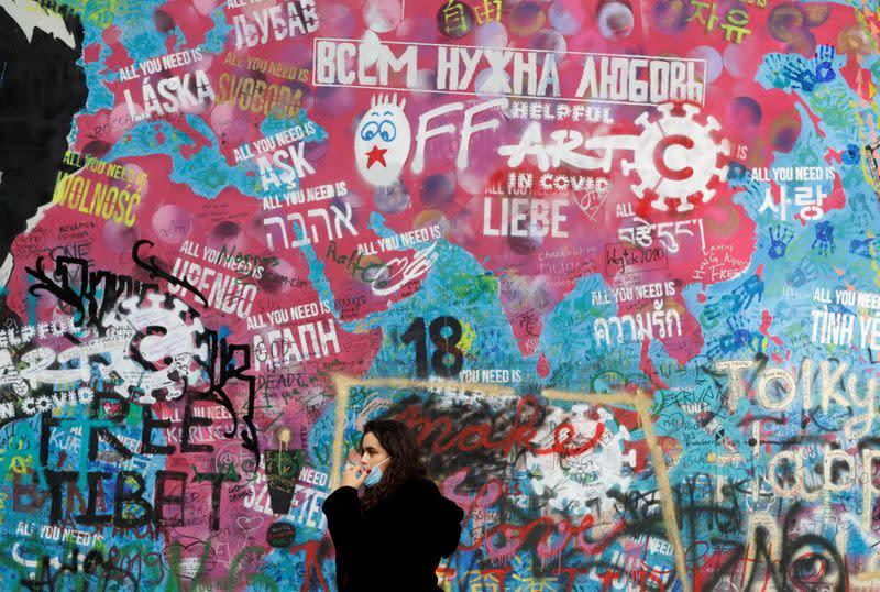A woman wearing a face mask walks in Prague