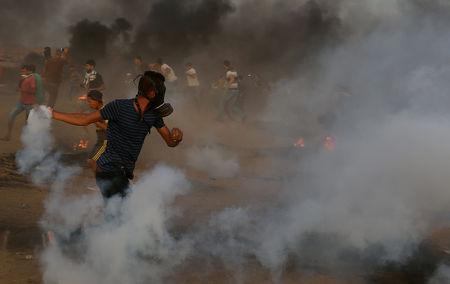 A Palestinian returns a tear gas canister during a protest calling for lifting the Israeli blockade on Gaza and demanding the right to return to their homeland, at the Israel-Gaza border fence in the southern Gaza Strip October 5, 2018. REUTERS/Ibraheem Abu Mustafa