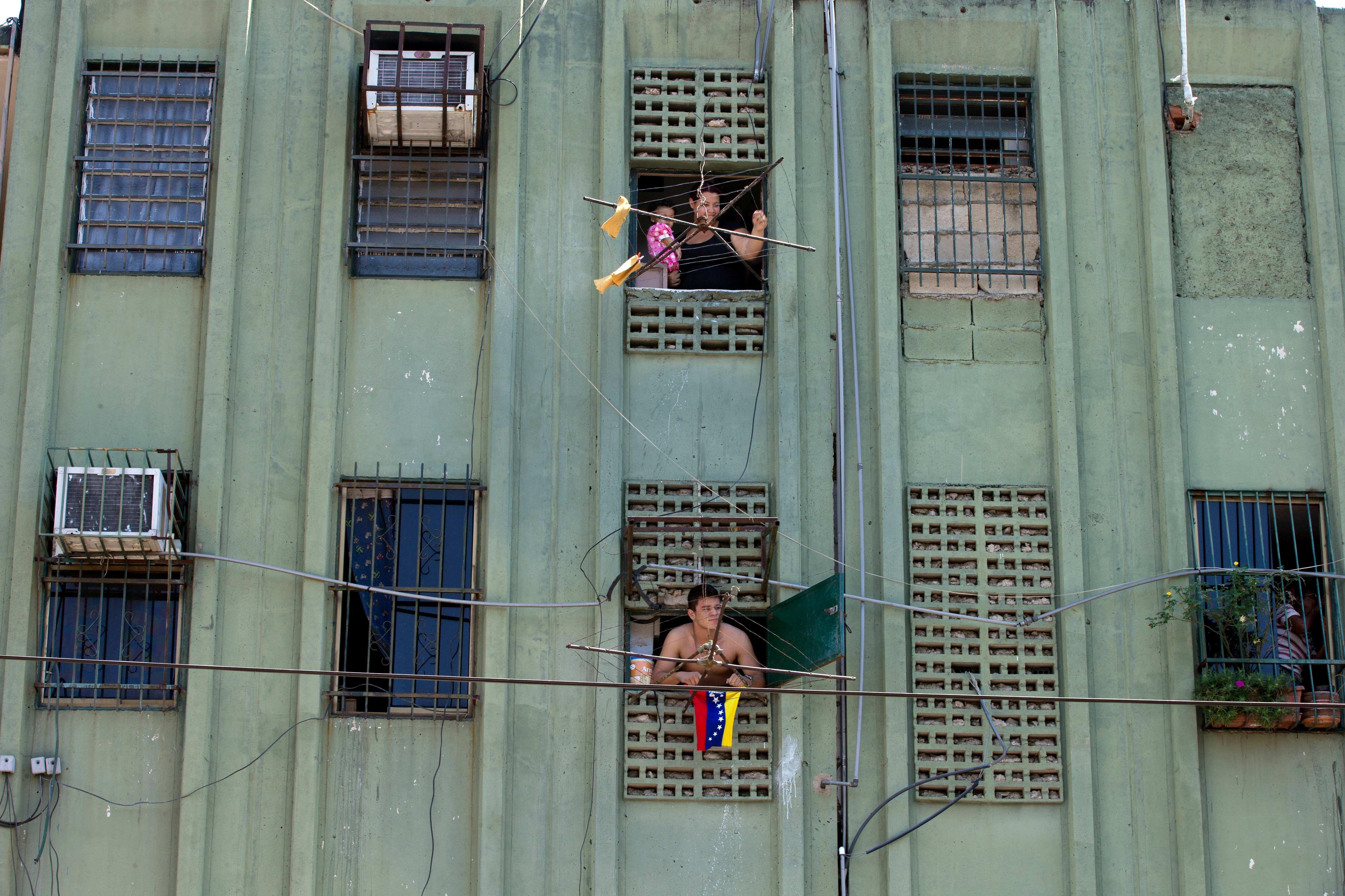 In this photo taken on Saturday, March 15, 2014. Residents look out from their apartments at a opposition protest at Isabelica neighborhood outside Valencia , Venezuela. The people of the poor district of La Isabelica were made to pay for taking to the streets in anti-government protests. More than a dozen masked men on motorcycles roared through, shooting up a barricade and killing a university student and a 42-year-old man painting his house. (AP Photo/Fernando Llano)