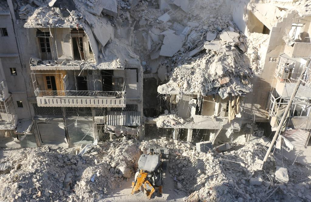 A tractor clears the rubble following Syrian govermnet forces air strikes in a rebel-held neighborhood of Aleppo on September 24, 2016