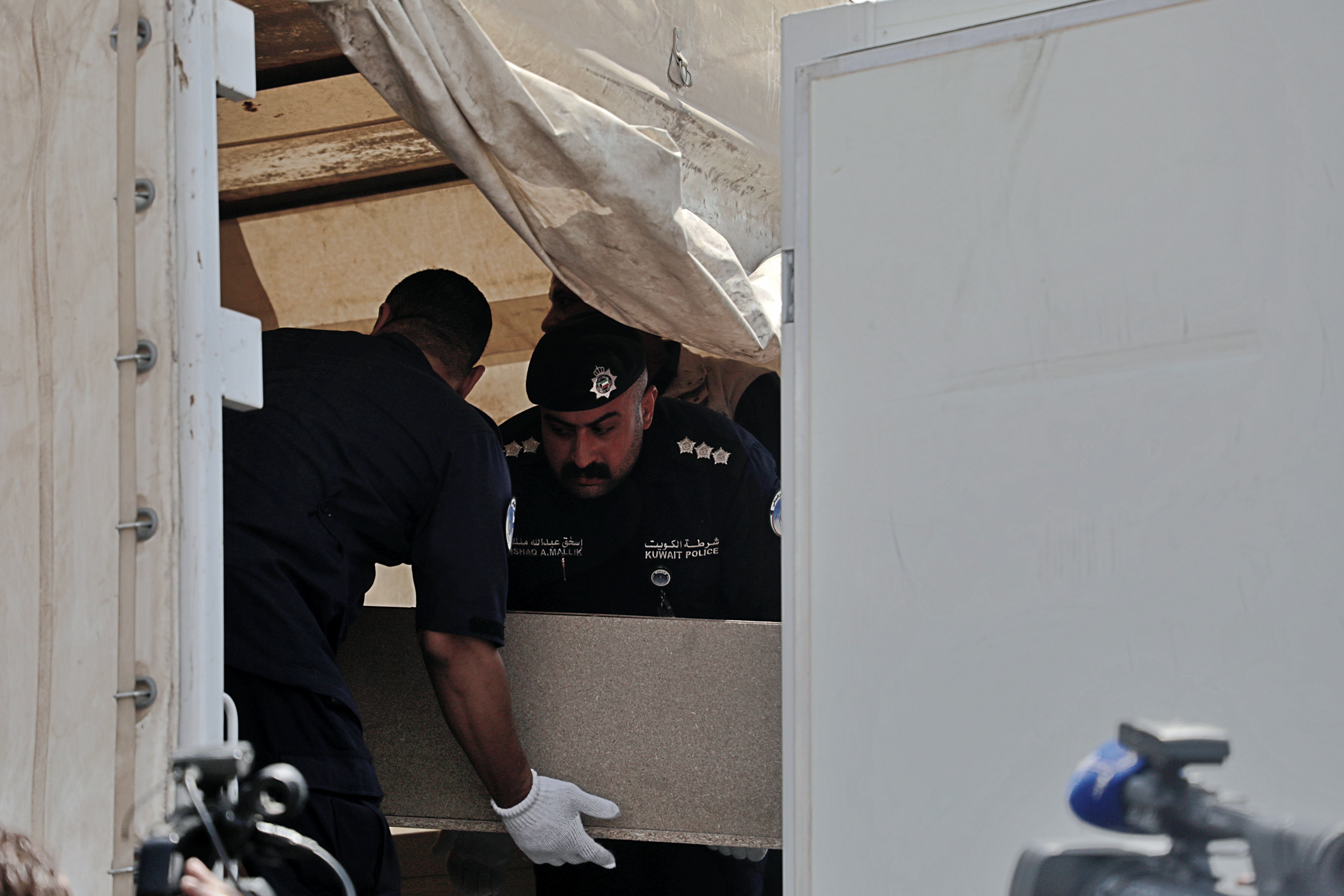 A casket holding the remains of one of 48 Kuwaiti citizens is transferred from an Iraqi truck to a Kuwaiti truck during a handover ceremony at the Safwan border crossing, in Iraq, Thursday, Aug. 8, 2019. Iraqi and Kuwaiti state media said Iraq has handed over to Kuwait the remains of 48 Kuwaitis who went missing during the 1991 Gulf War. (AP Photo)
