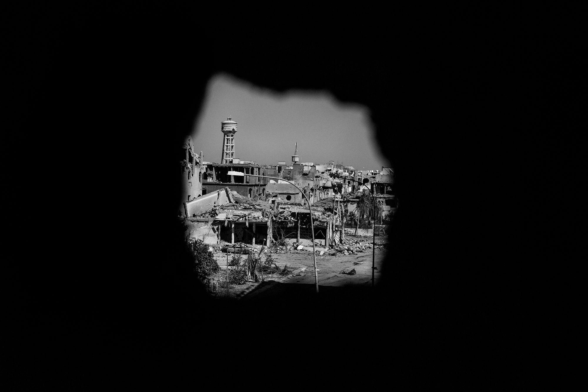 <p>View of an area controlled by Islamic State (ISIS) militants, seen through a sniper hole in Sirte, Libya, in September 2016. (Photo: Manu Brabo/MeMo for Yahoo News) </p>