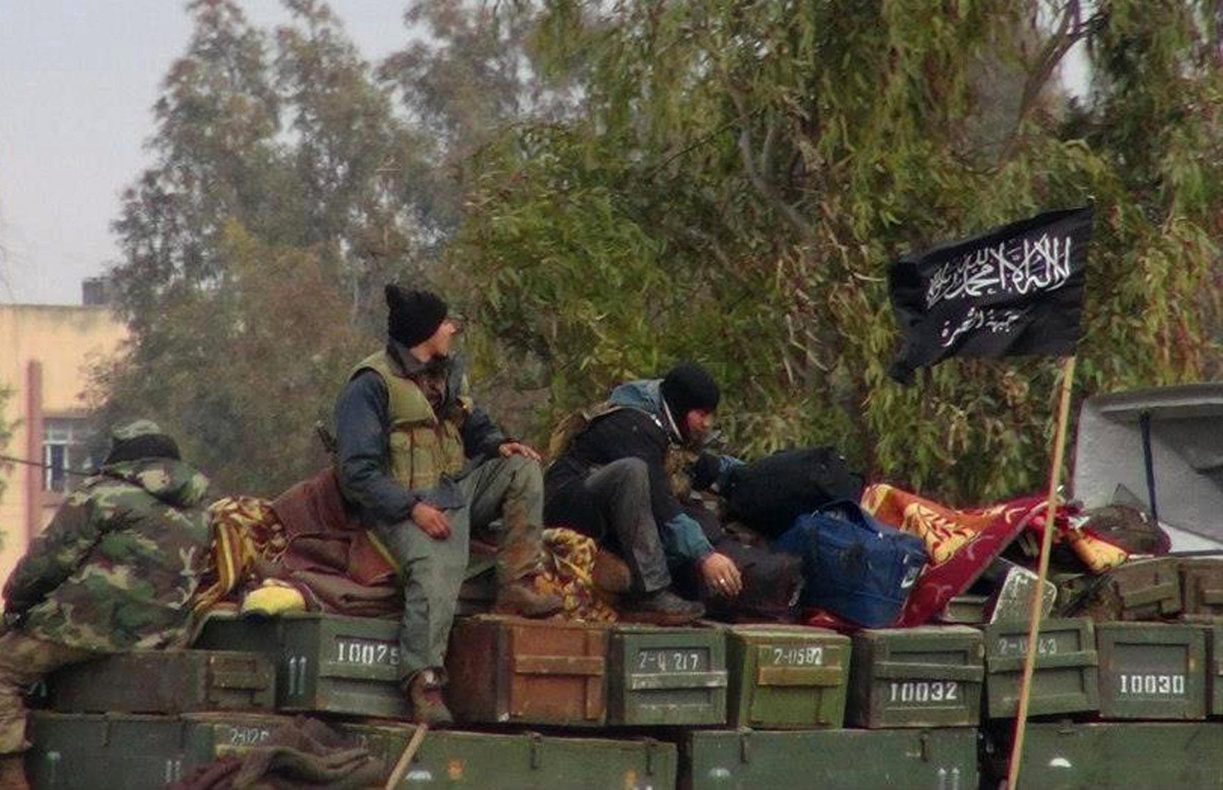 """FILE - In this Friday, Jan. 11, 2013 file citizen journalism image provided by Edlib News Network, ENN, which has been authenticated based on its contents and other AP reporting, shows rebels from al-Qaida affiliated Jabhat al-Nusra, as they sit on a truck full of ammunition, at Taftanaz air base, that was captured by the rebels, in Idlib province, northern Syria. Al-Qaida's branch in Iraq said it has merged with Syria's extremist Jabhat al-Nusra, a move that shows the rising confidence of radicals within the Syrian rebel movement and is likely to trigger renewed fears among its international backers. Arabic on the flag, right, reads, """"There is no God only God and Mohamad his prophet, Jabhat al-Nusra."""" (AP Photo/Edlib News Network ENN, File)"""