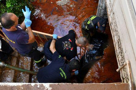 Rescue workers carry the body bag of a drowned woman away from her flooded house in Kalamata, Greece September 7, 2016. Eurokinissi/Dimitris Plemmenos via REUTERS