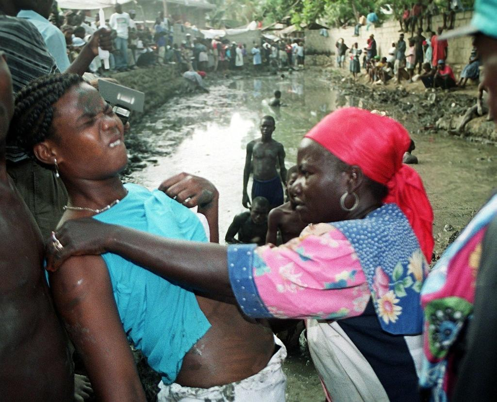 File picture shows a Voodoo priestess (R) treating a sick woman during a ritual ceremony in Cap-Haitian, north of Port-au-Prince