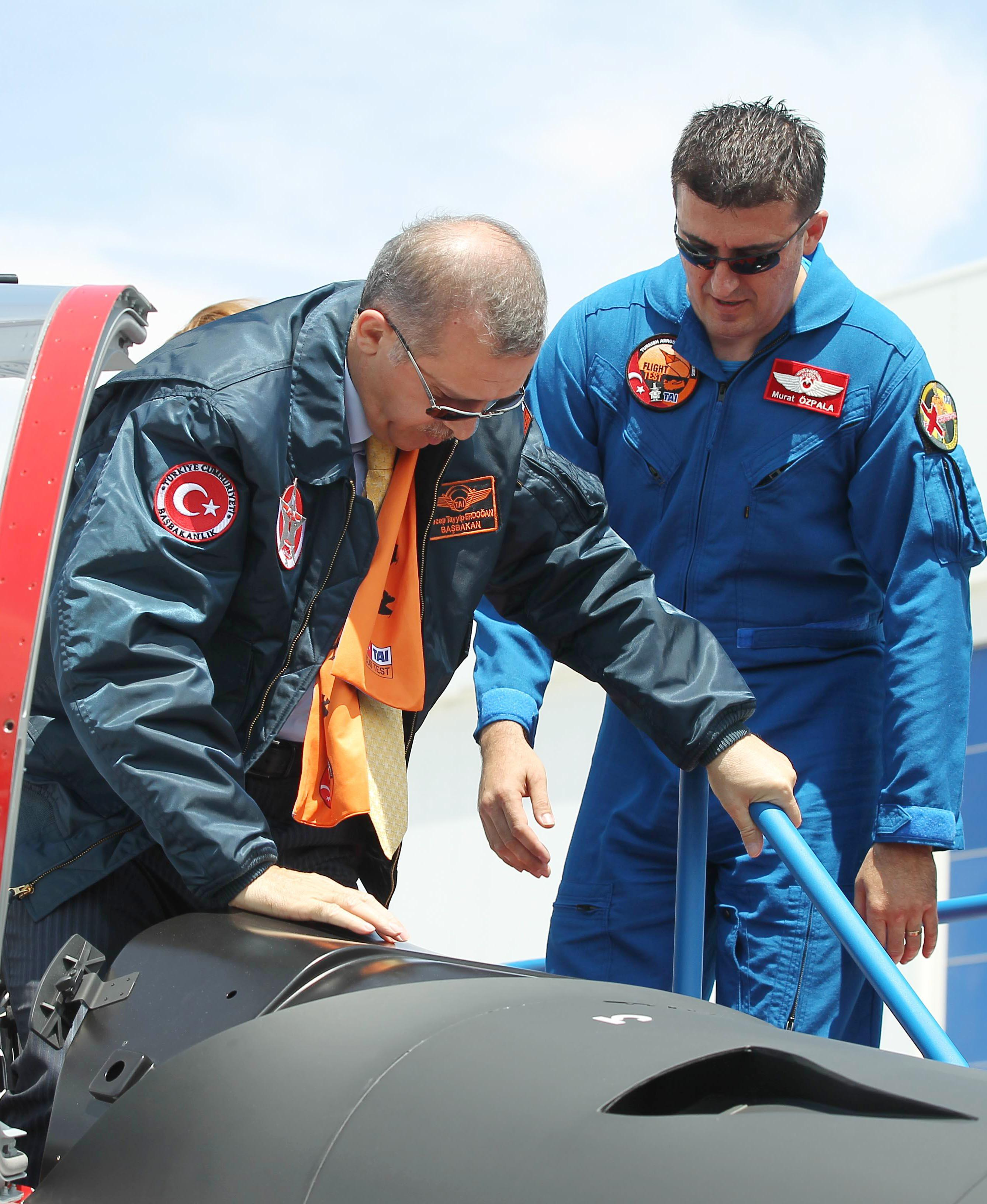 "Turkish Prime Minister Recep Tayyip Erdogan, left, gets into cockpit of a Hurkus (Freebird), Turkey's first locally produced military training plane, a two-seat turboprop plane, unveiled during a ceremony outside Ankara, Turkey, Wednesday, June 27, 2012. Erdogan kept up his pressure on Syria on Wednesday, saying ""we would never hesitate to respond with all our power to hostile acts, attacks and threats against us."" AP Photo)"