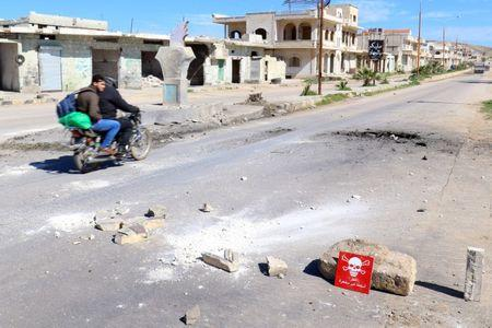 """Men ride a motorbike past a hazard sign at a site hit by an airstrike on Tuesday in the town of Khan Sheikhoun in rebel-held Idlib, Syria April 5, 2017. The hazard sign reads, """"Danger, unexploded ammunition"""". REUTERS/Ammar Abdullah"""
