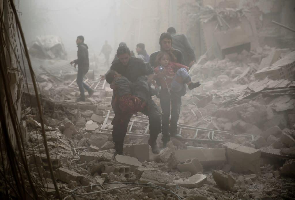 People evacuate victims following air strikes on Douma in the eastern Ghouta region on December 13, 2015 (AFP Photo/Sameer al-Doumy)