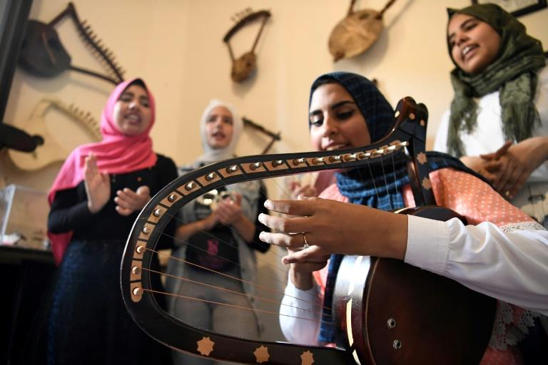 Iman Haddo (C), a                                                  20-year-old musician,                                                  says she instantly fell                                                  in love with the                                                  semsemia when she was a                                                  teenager after attending                                                  a local concert with her                                                  father. (AFP                                                  Photo/Khaled DESOUKI)