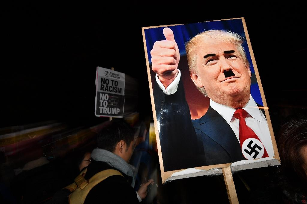 A demonstrator holds a placard showing a picture of US President-elect Donald Trump modified to add a swastika and an Adolf Hitler-style moustache during a protest outside the US Embassy in London (AFP Photo/Ben Stansall)