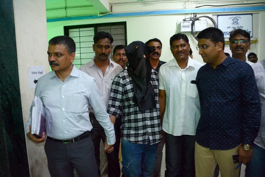Police escort alleged call centre scam mastermind Sagar Thakkar (C), arrested on his return to India after he fled to Dubai