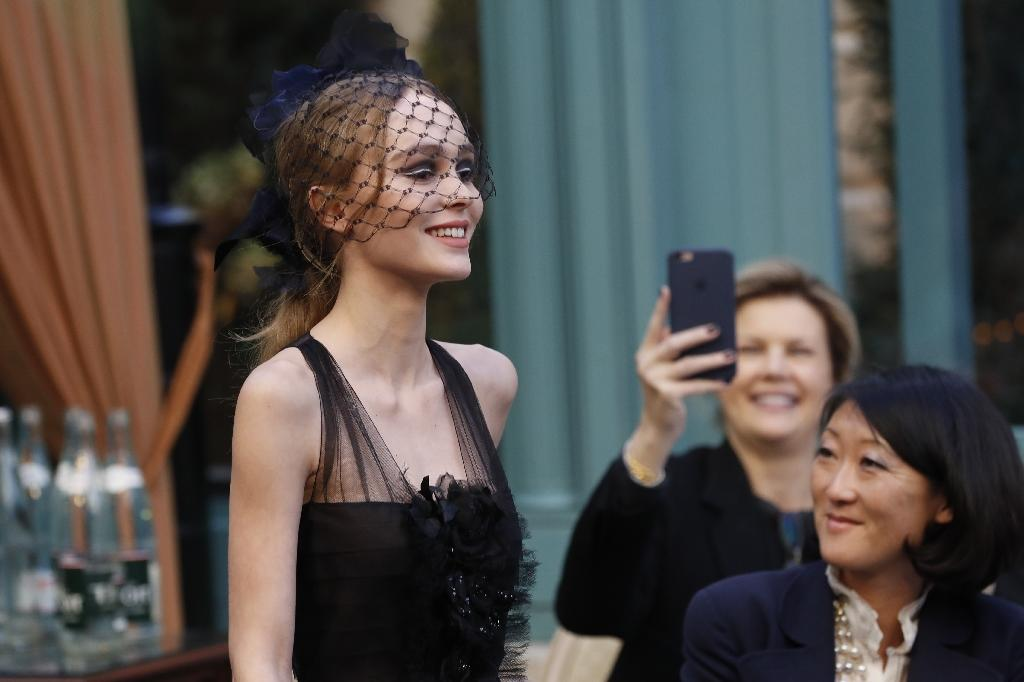 French-American actress and model Lily-Rose Depp presents a creation for Chanel, during the 13th Métiers d'Art show in Paris (AFP Photo/PATRICK KOVARIK)