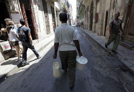 A man carries buckets of water in Havana in this April 13, 2011 file photo. REUTERS/Enrique De La Osa/Files