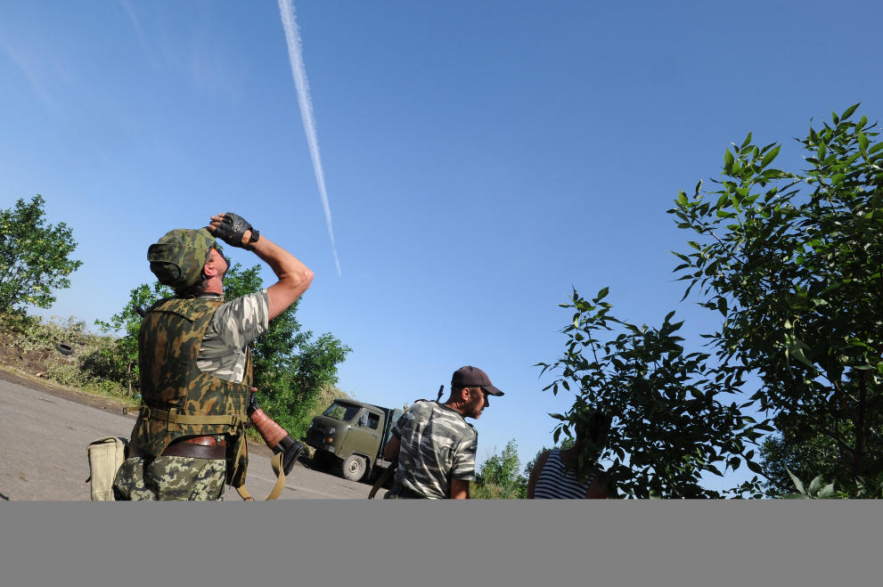 Pro-Russia militants look overhead at a Ukrainian army plane as they exchange fire near the town of Marynivka, 100 km east of Donetsk, on July 16, 2014 (AFP Photo/Dominique Faget)