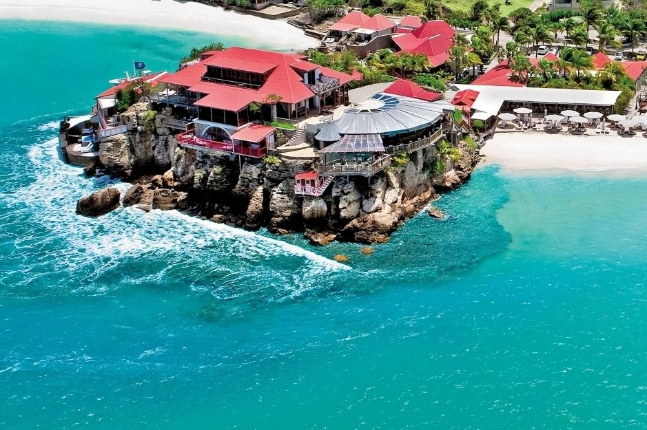 """<p>Perched on a rocky promontory of St Jean Bay and surrounded by white coral sandy beaches, clear blue sea and a beautiful coral reef rife with wild sea life, <a href=""""http://www.edenrockhotel.com/eng/home/"""" target=""""_blank"""">Hotel Eden Rock</a> is the epitome of glamour in the French Caribbean. The hotel features 34 rooms and suites dotted along the beach or set within lush green gardens. Unique signature suites include the ultra-luxe Villa Nina and world-famous Villa Rockstar, which comes with its own recording studio. The new 200-square-metre Christopher Columbus Suite features a spectacular cliff-edge positioning and has the best views in the house over the sea and the island of St Barths behind. Rates at Eden Rock start from €650 per night.</p>"""