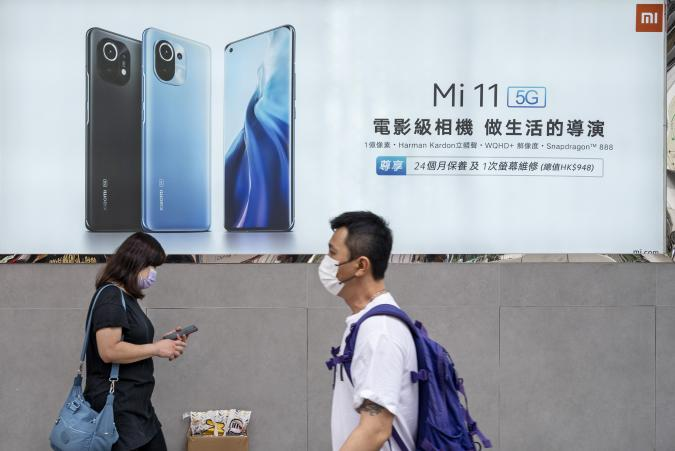 HONG KONG, CHINA - 2021/03/31: Pedestrians walk past the Xiaomi Mi 11 5G smartphone advertisement at its flagship store in Hong Kong. (Photo by Budrul Chukrut/SOPA Images/LightRocket via Getty Images)