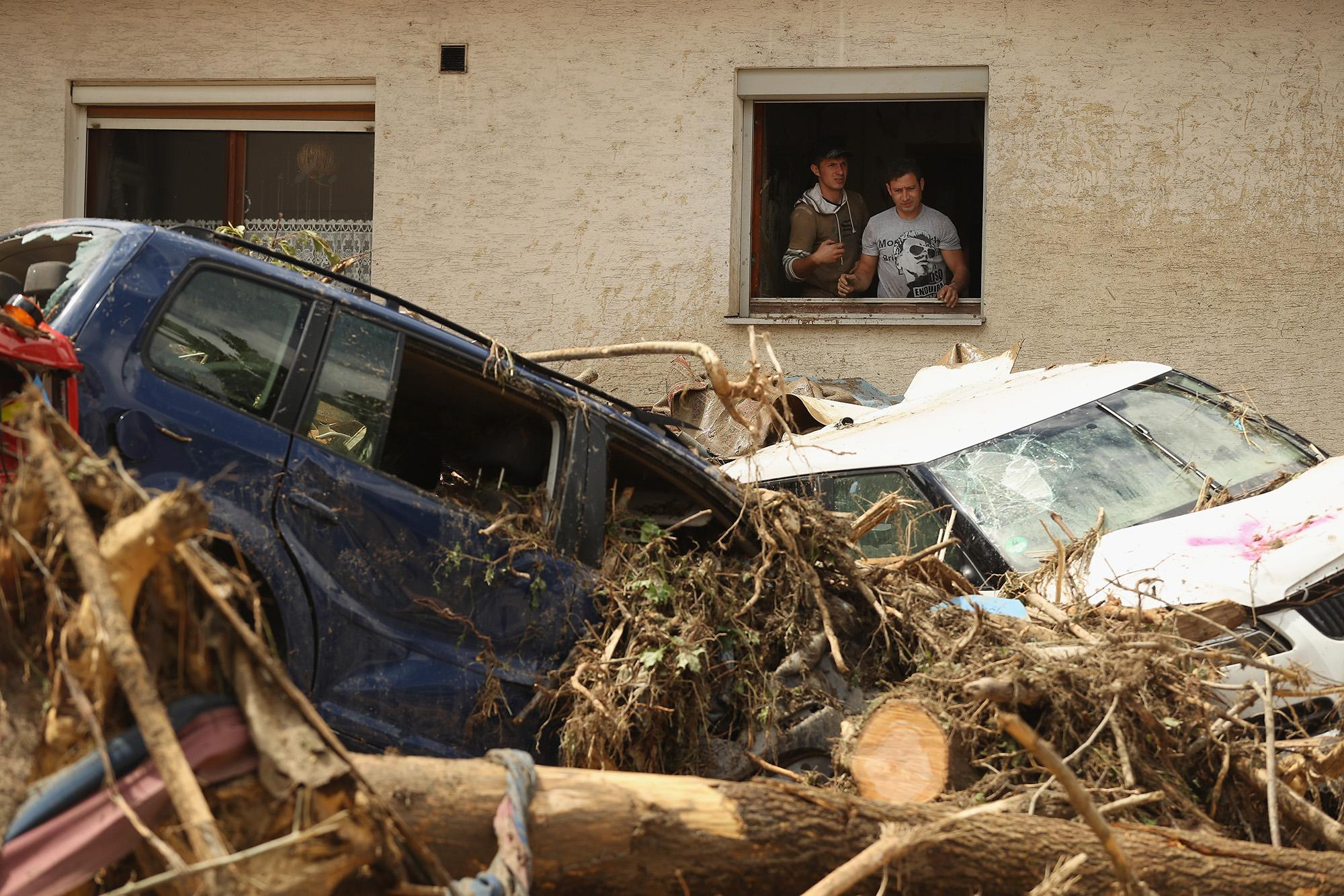 <p>Two men throw ruined household items from a window on May 30, 2016, next to cars smashed by a flood the night before in Braunsbach, Germany. (Sean Gallup/Getty Images) </p>