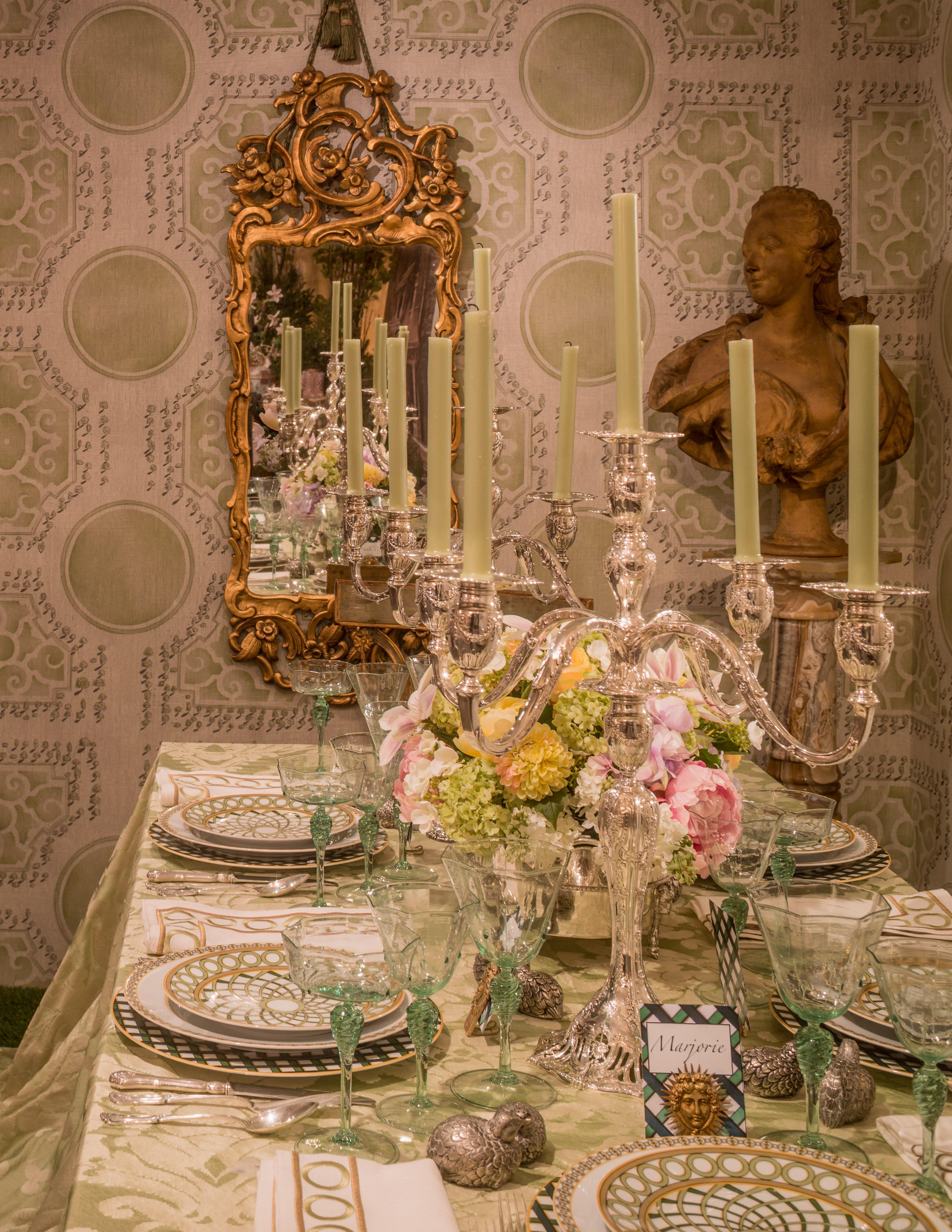 """Corrigan's literal centerpiece is a pair of breathtaking silver candelabras from Post's collection, around which he built a French garden scene. """"My inspiration was the gardens here at Hillwood,"""" he explains. """"I love the greenhouse and the gardens, so I riffed on that using this new wallpaper I designed for Fromental inspired by the gardens at Versailles, handpainted on silk. On the ground I put AstroTurf, and the garden theme continued with my Jardin Français china for Royal Limoges."""" Corrigan added a personal touch to the tablescape by way of Murano glassware that his grandmother purchased on her Venetian honeymoon. It's the china, of all things, that gives Corrigan's setting the same balance of casual and chic for which Moss aimed: """"The best thing about these plates?"""" Corrigan asks, holding one up with a grin: """"They're the first fine china in the world with gold that you can put in the dishwasher and microwave! And I think that's so important because people have this beautiful china but they never use it because they can't dishwash it."""" Marjorie would certainly have been impressed."""