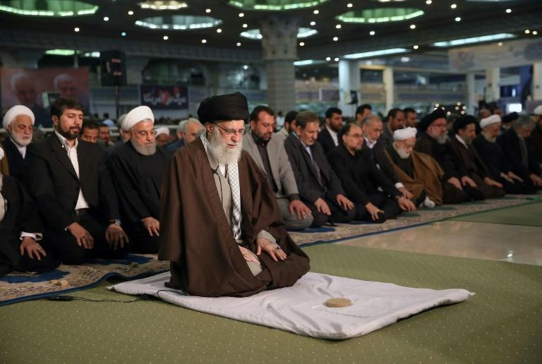 """Iran's Supreme Leader Ayatollah Ali Khamenei on Friday labelled the governments of Britain, France and Germany """"American lackeys"""" in a speech as he led the main weekly Muslim prayers in Tehran for the first time since 2012 on January 17, 2020, shows Khamenei (C) leading Friday prayers during a ceremony at the capital Tehran's Grand Mosallah (mosque), while flanked by President Hassan Rouhani (C-L, behind)"""