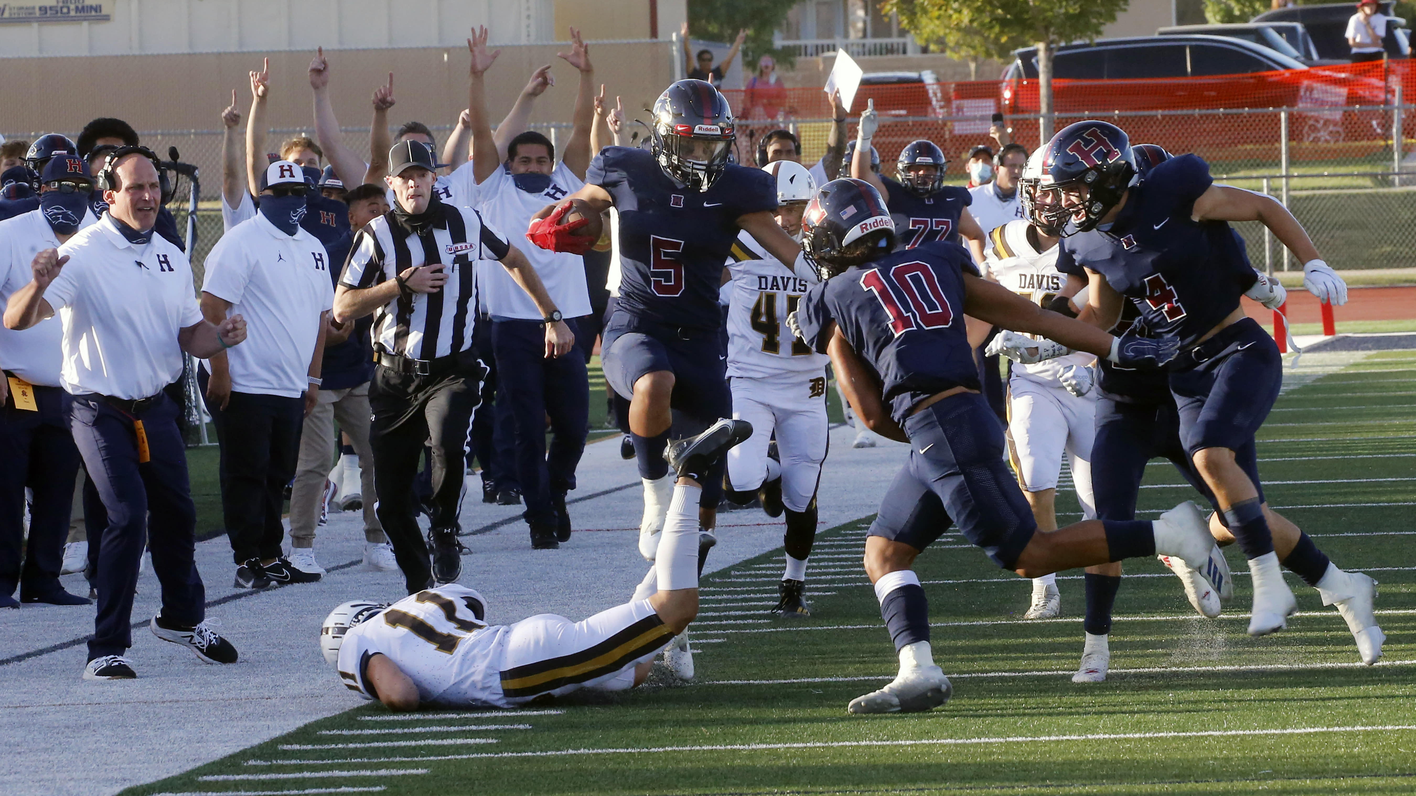 Herriman's Brock Hollingsworth (5) hurdles Jackson Leaver (11) during a high school football game, on Thursday, Aug. 13, 2020, in Herriman, Utah. Utah is among the states going forward with high school football this fall despite concerns about the ongoing COVID-19 pandemic that led other states and many college football conferences to postpone games in hopes of instead playing in the spring. (AP Photo/Rick Bowmer)