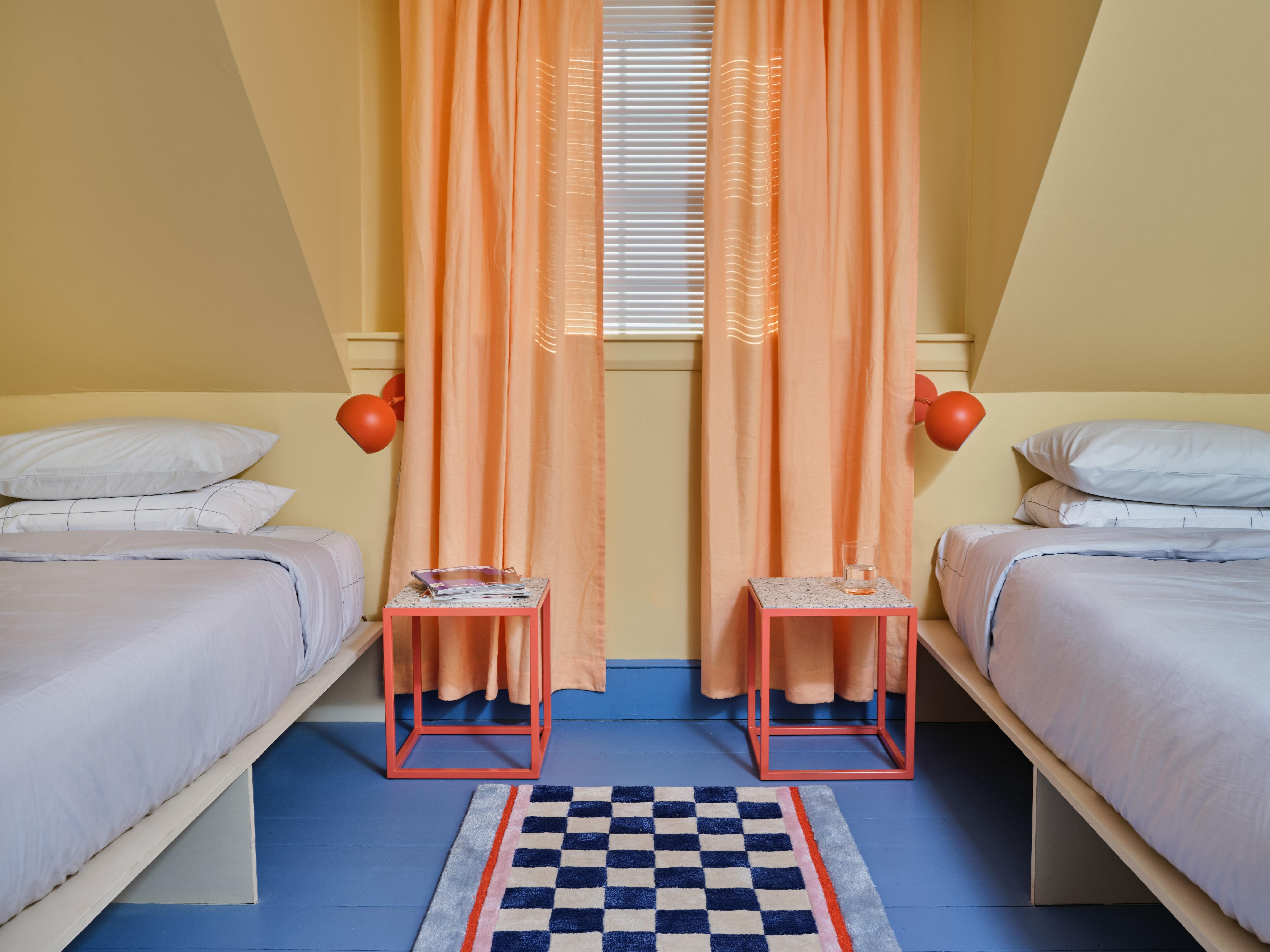 """This pale yellow guest bedroom with its bright blue floors and coral red accents is just one colorful moment in this <a href=""""https://www.architecturaldigest.com/story/this-19th-century-home-is-now-a-rainbow-hued-vacation-rental?mbid=synd_yahoo_rss"""" rel=""""nofollow noopener"""" target=""""_blank"""" data-ylk=""""slk:Maine home"""" class=""""link rapid-noclick-resp"""">Maine home</a>—the brainchild of <a href=""""https://www.architecturaldigest.com/story/pieces-unapologetically-playful-brooklyn-apartment?mbid=synd_yahoo_rss"""" rel=""""nofollow noopener"""" target=""""_blank"""" data-ylk=""""slk:Jenny Kaplan"""" class=""""link rapid-noclick-resp"""">Jenny Kaplan</a>, Chris Corrado, and Taisha Coombs, founders of the Brooklyn-based creative agency <a href=""""http://www.anaestheticpursuit.com/"""" rel=""""nofollow noopener"""" target=""""_blank"""" data-ylk=""""slk:An Aesthetic Pursuit"""" class=""""link rapid-noclick-resp"""">An Aesthetic Pursuit</a>, and its sister venture, the home furnishings line <a href=""""https://pieceshome.com/"""" rel=""""nofollow noopener"""" target=""""_blank"""" data-ylk=""""slk:Pieces"""" class=""""link rapid-noclick-resp"""">Pieces</a>."""