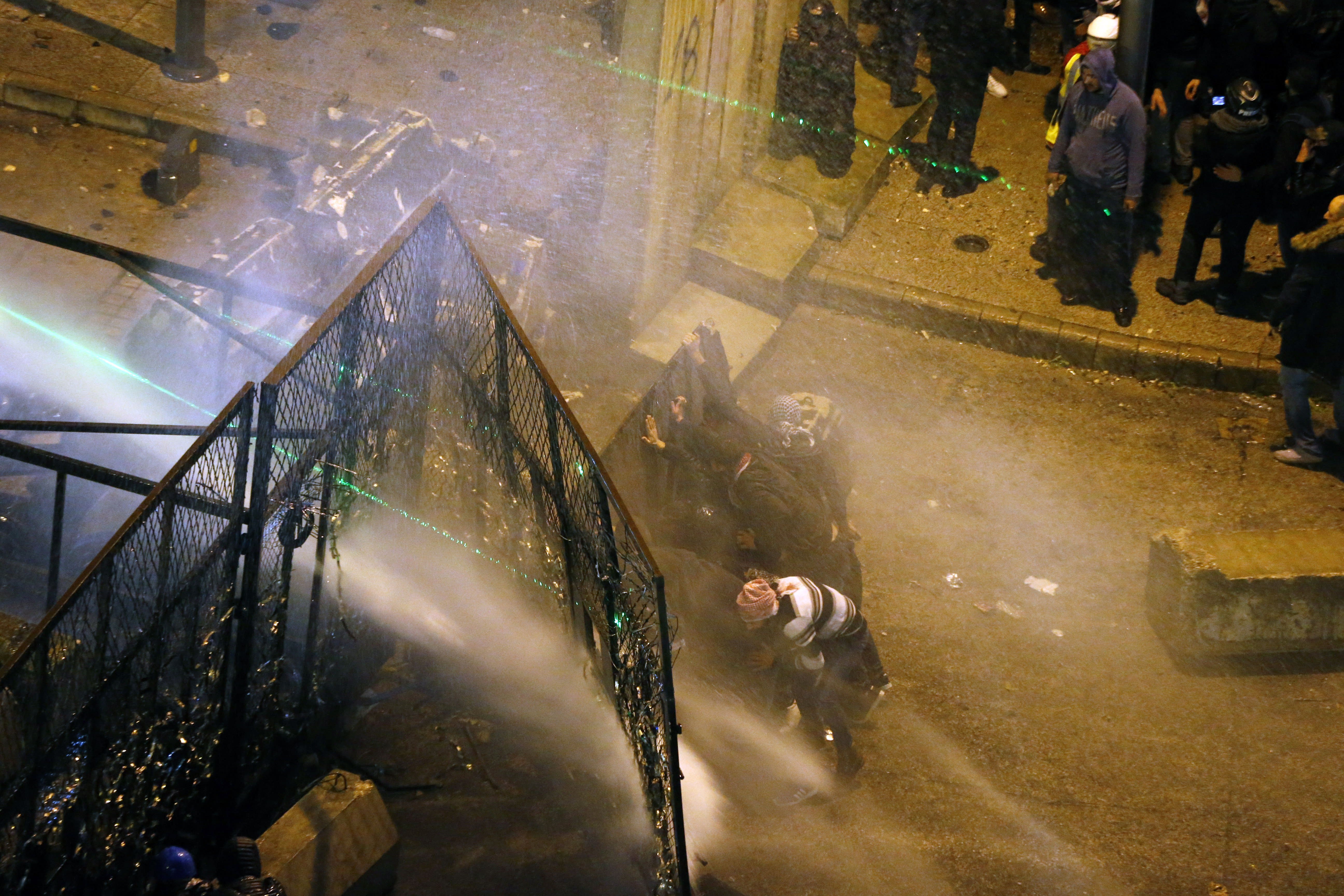 Riot police sprayed anti-government protesters with water cannons as they try to cross to the central government building during ongoing protests in Beirut, Lebanon, Saturday, Jan. 25, 2020. Hundreds of Lebanese gathered outside the central government building to reject the newly formed Cabinet, while some protesters breached tight security erected around it, removing a metal gate and barbed wire prompting a stream of water cannons from security forces. (AP Photo/Bilal Hussein)