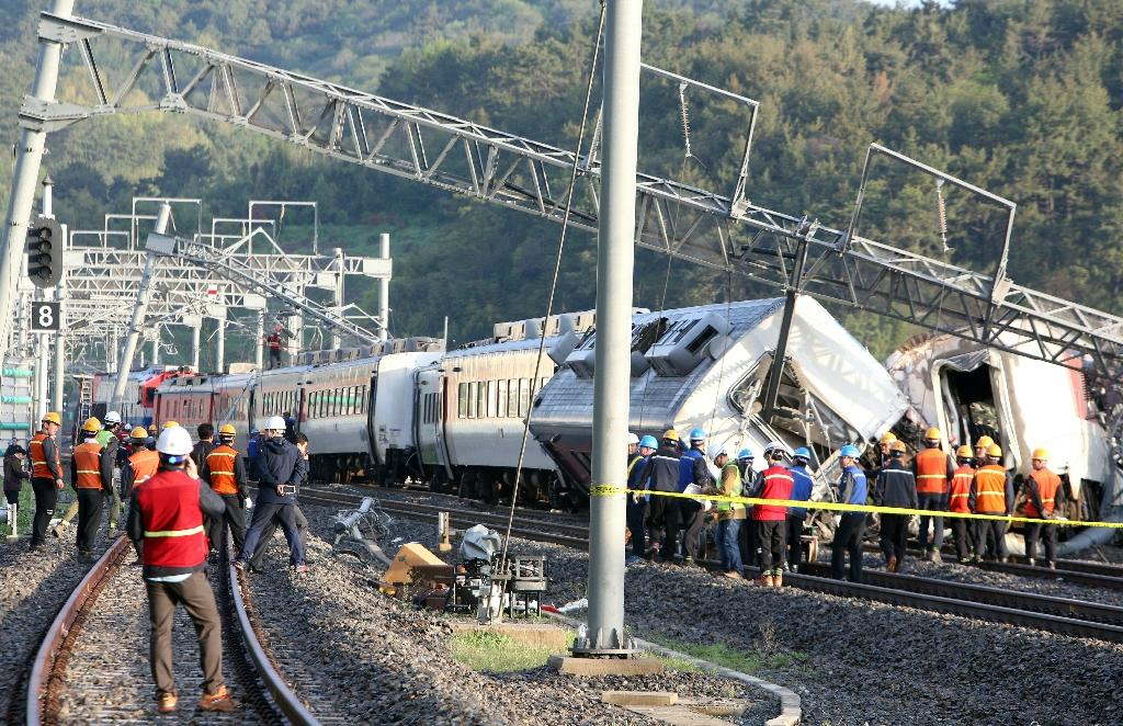 South Korea railway workers struggle to put a derailed passenger train back on track in the southern port city of Yeosu on April 22, 2016