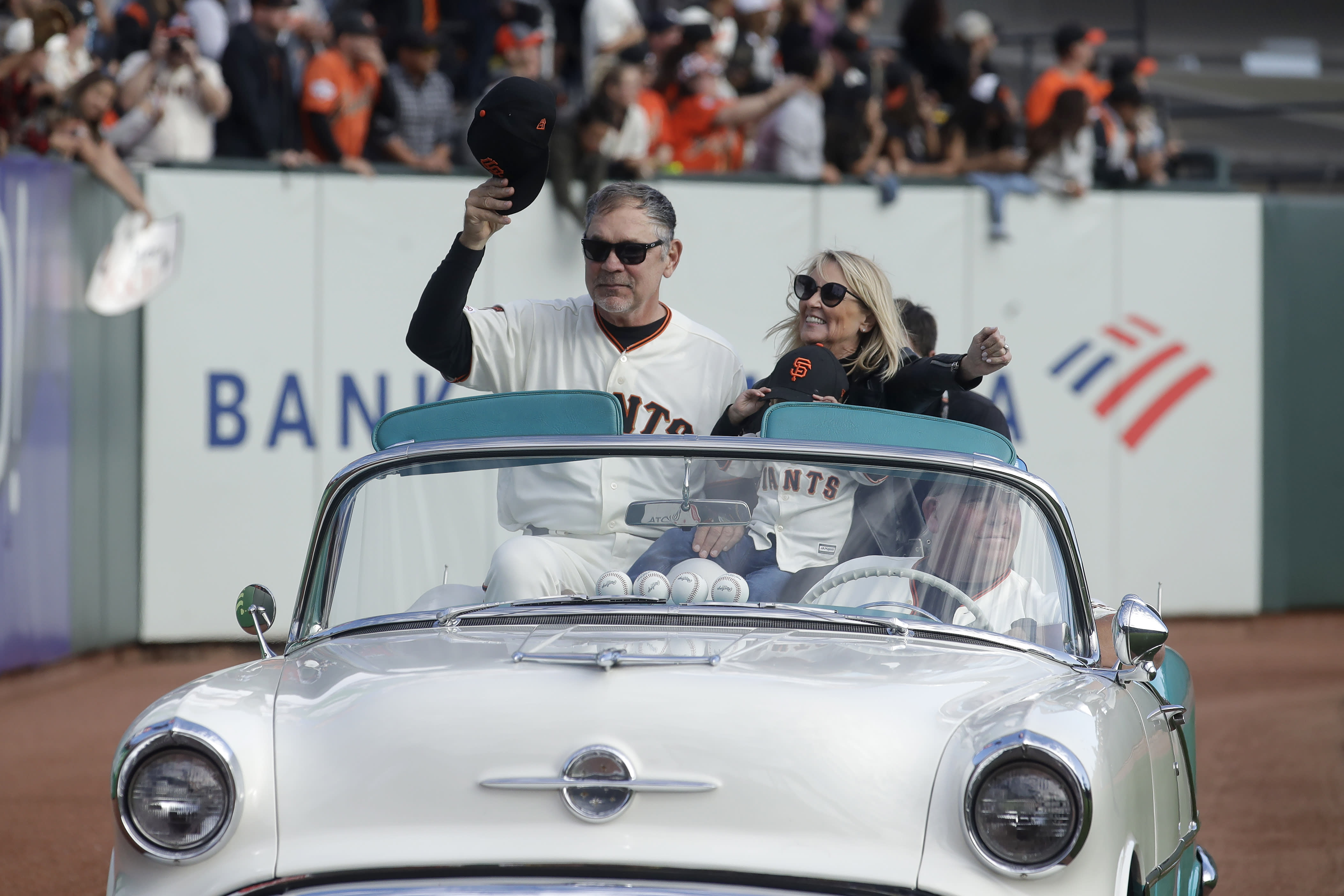 San Francisco Giants manager Bruce Bochy, left, is driven around the field with his wife Kim during a ceremony honoring Bochy after a baseball game between the Giants and the Los Angeles Dodgers in San Francisco, Sunday, Sept. 29, 2019. (AP Photo/Jeff Chiu, Pool)