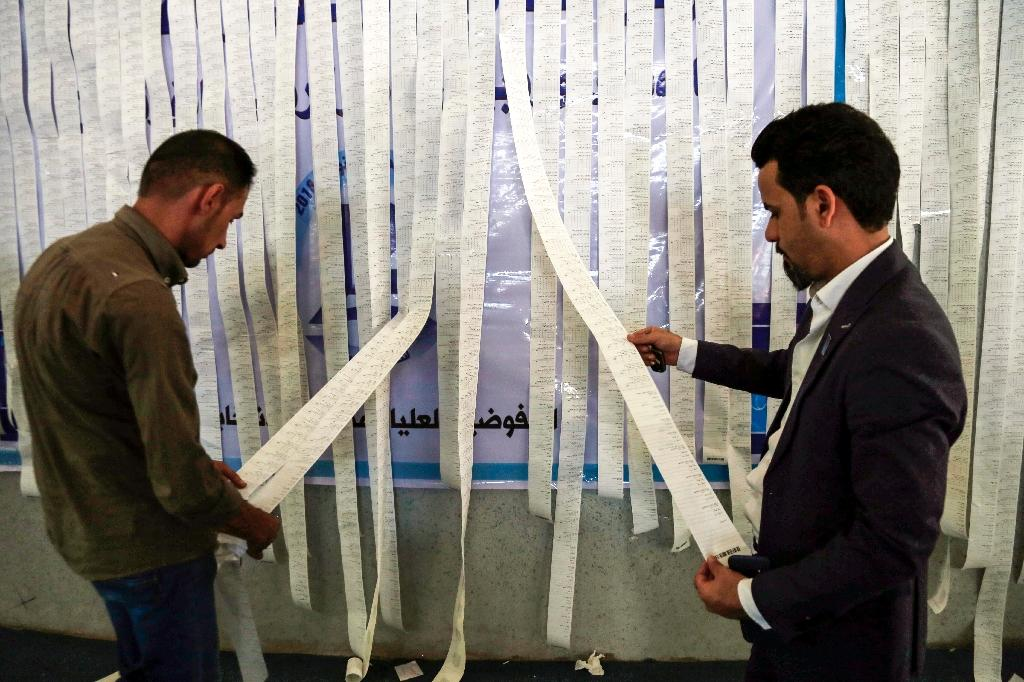 Iraqi electoral commission employees examine electronic counting machine print-outs in Najaf on May 13, 2018