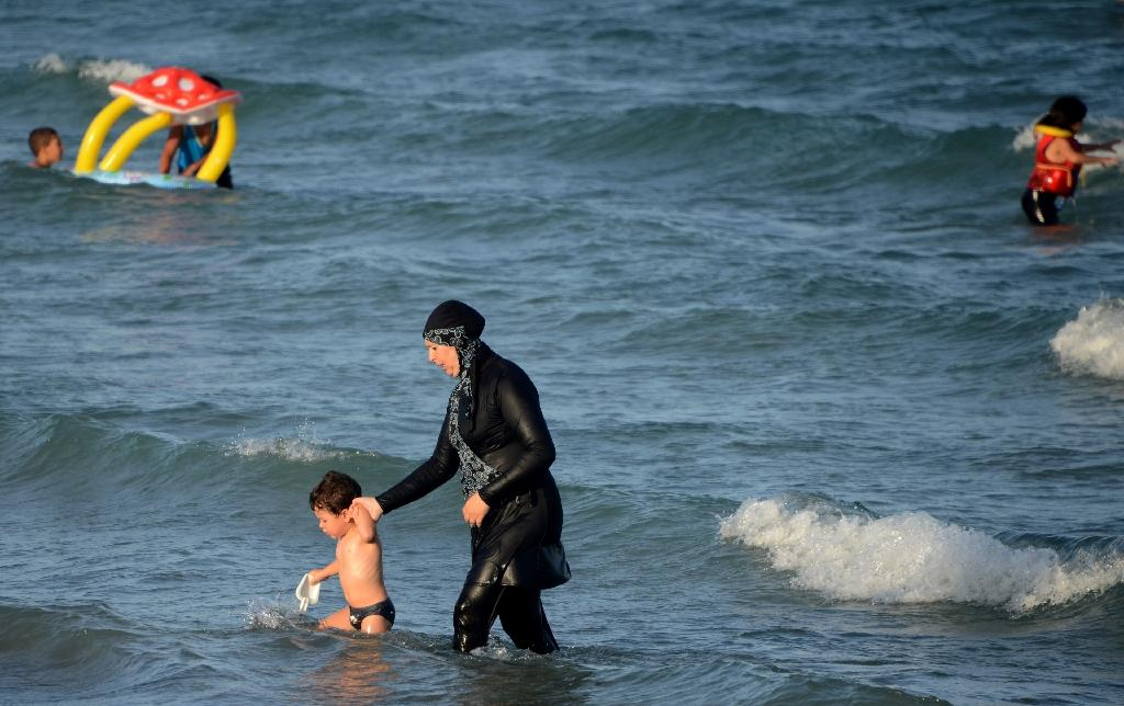 "A Tunisian woman wearing a ""burkini"", a full-body swimsuit designed for Muslim women, walks in the water with a child on August 16, 2016 at Ghar El Melh beach near Bizerte, north-east of the capital Tunis (AFP Photo/Fethi Belaid)"
