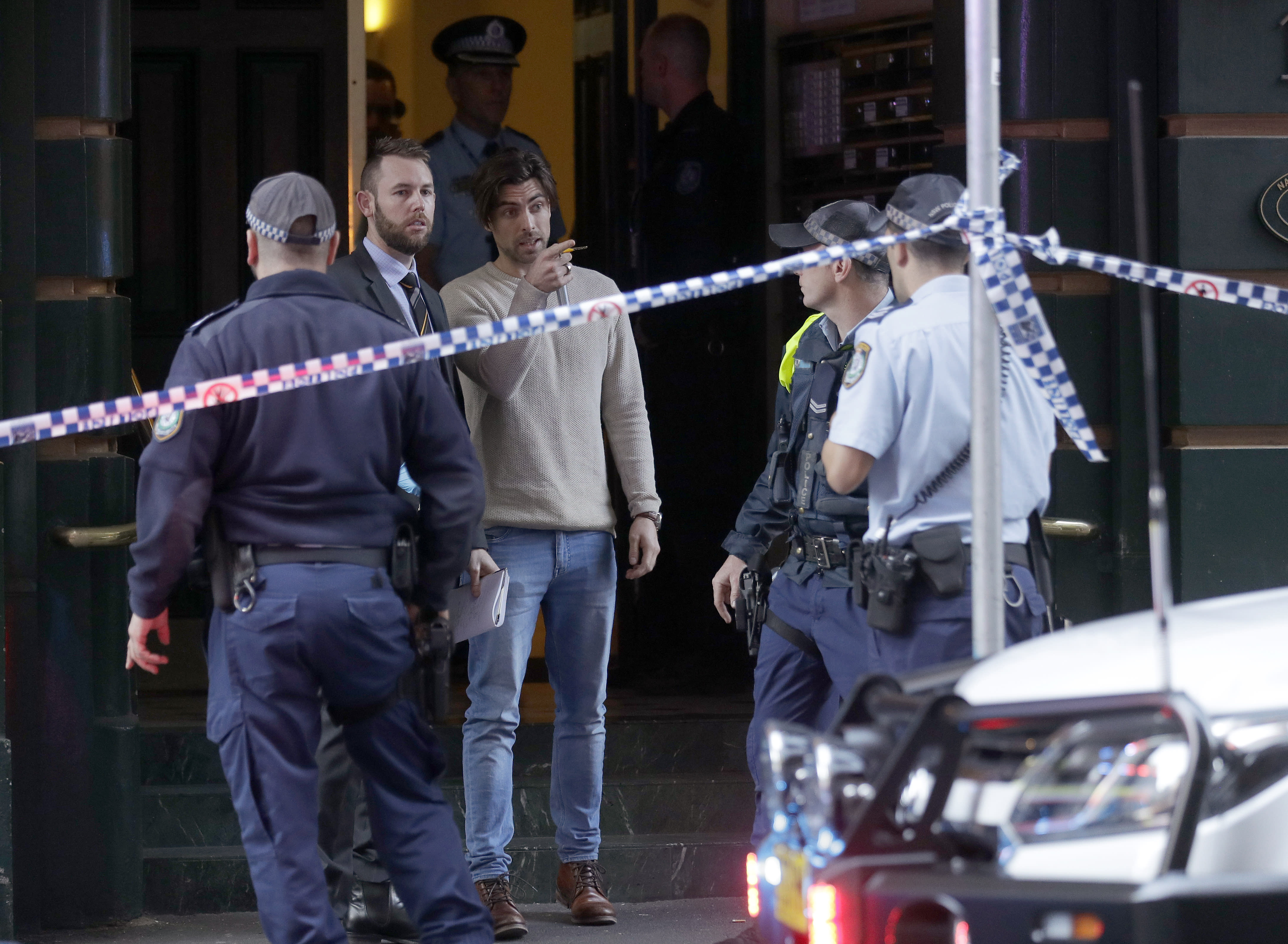 """A man, center, points as he assists police at a building where a person has been found deceased after a man attempted to stab multiple people in Sydney, Australia, Tuesday, Aug. 13, 2019. Police and witnesses say a knife-wielding man yelling """"Allahu akbar,"""" or """"God is great,"""" has attempted to stab several people before being arrested, with one person taken to a hospital. (AP Photo/Rick Rycroft)"""