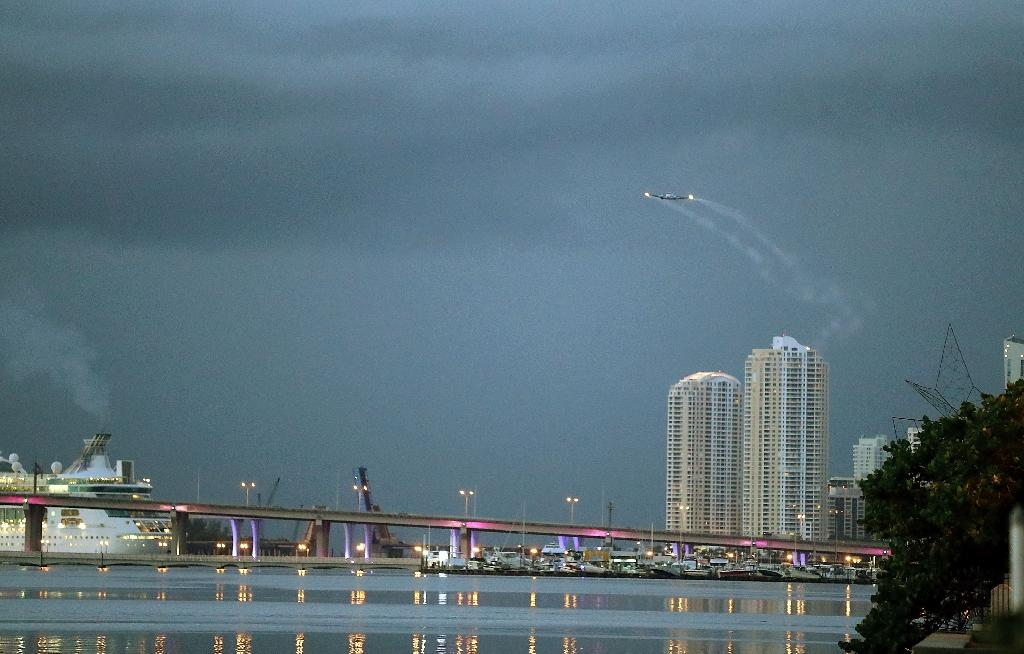 A plane sprays pesticide over parts of the city of Miami in the hope of controlling and reducing the number of mosquitos on August 12, 2016 (AFP Photo/Joe Raedle)