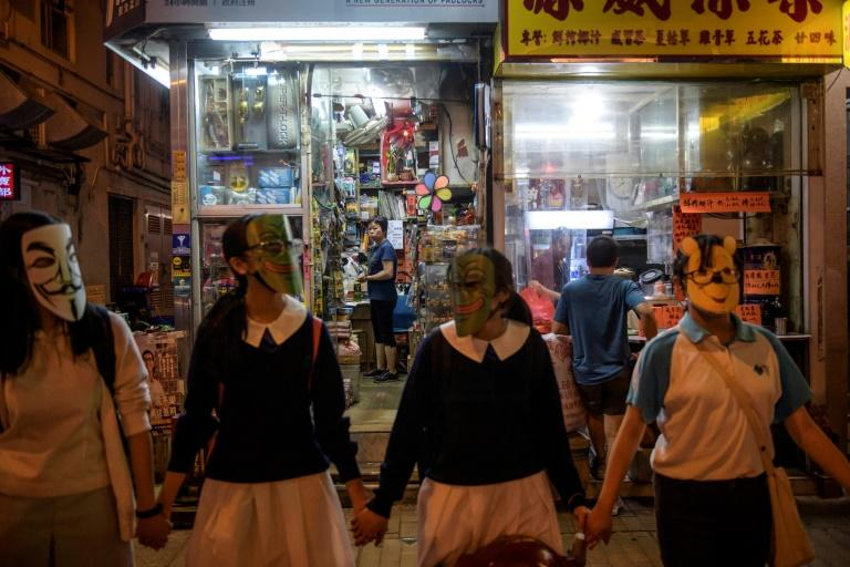 A shopkeeper in Hong Kong watches masked students and protesters gather to form a human chain involving thousands, in opposition to a colonial-era emergency law that bans face masks at demonstrations
