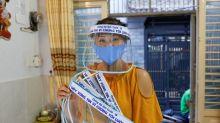 Vietnamese hat seller turns to homemade face shields in virus fight