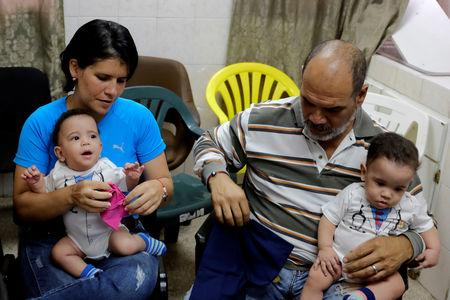Joel Martinez and his daughter Cristina carry her sons Manuel and Miguel at the Concepcion Palacios Hospital in Caracas, Venezuela September 13, 2018. Picture taken September 13, 2018. REUTERS/Marco Bello