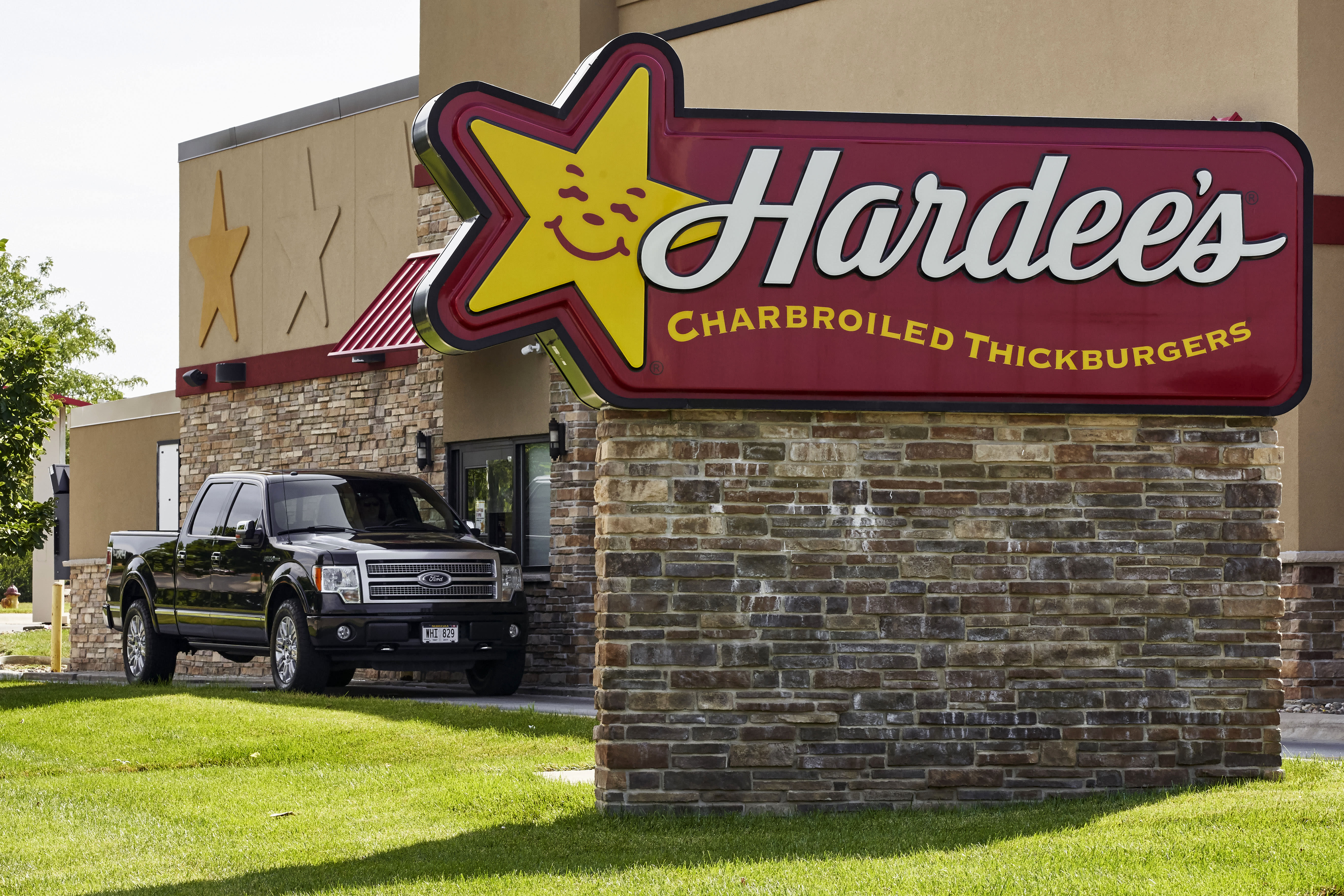 A vehicle approaches the drive-thru window at a Hardee's fast food restaurant in Omaha, Neb., Tuesday, July 7, 2020. Some big corporate names are on the government's list of 650,000 recipients of coronavirus relief loans despite the controversy that prompted other high-profile businesses to return billions of dollars in loan. Among the companies on the list are Boddie-Noell Enterprises, owner of 346 Hardee's restaurants, who received between $5 million and $10 million. (AP Photo/Nati Harnik)