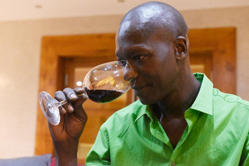 """Senegalese grower and winemaker Mokhsine Diouf tastes the wine from the """"Clos des Baobabs"""" vineyard in Nguekhokh on September 15, 2015 (AFP Photo/Seyllou)"""