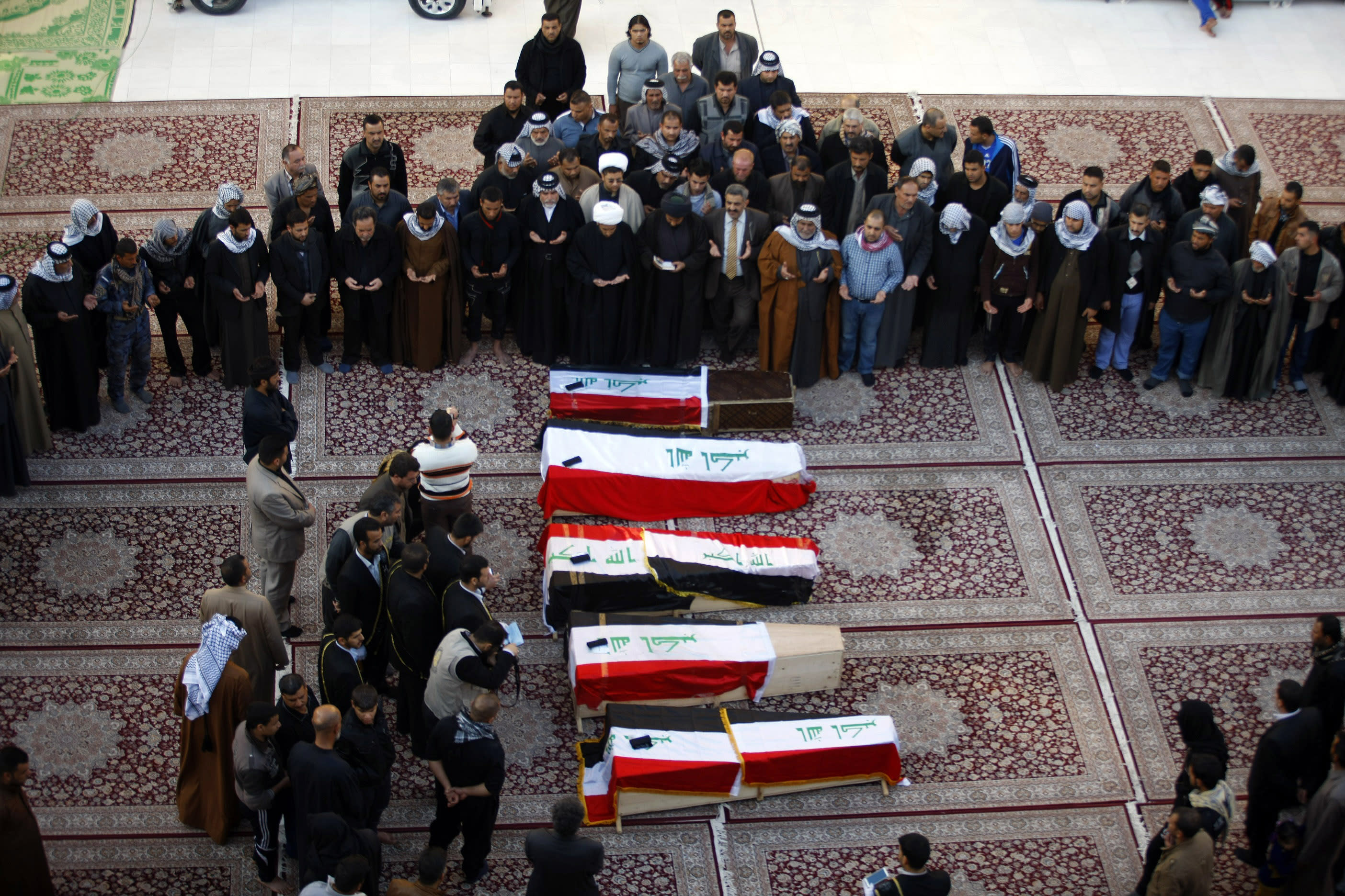 Mourners pray over coffins draped with Iraqi flags for Iraqi soldiers killed by al-Qaida militants in Anbar province during their funeral procession inside the shrine of Imam Ali in Najaf, 100 miles (160 kilometers) south of Baghdad, Iraq, Tuesday, Jan. 21, 2014. Security forces on Monday found the bodies of four soldiers from an elite special forces unit who were captured by militants near Fallujah about two weeks ago. The executed bodies were found in al-Bubali village one day after it was retaken by Iraqi troops.(AP Photo/Jaber al-Helo)
