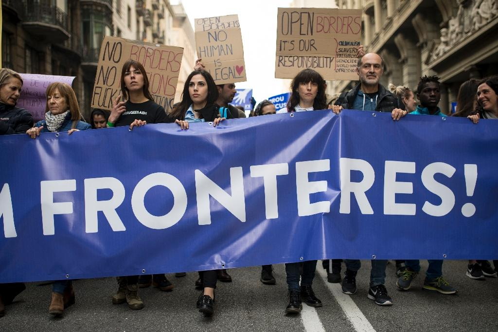 """Demonstrators hold a banner reading """"Let's open borders"""" as they demand the welcoming of refugees in Barcelona on February 18, 2017 (AFP Photo/Josep Lago)"""