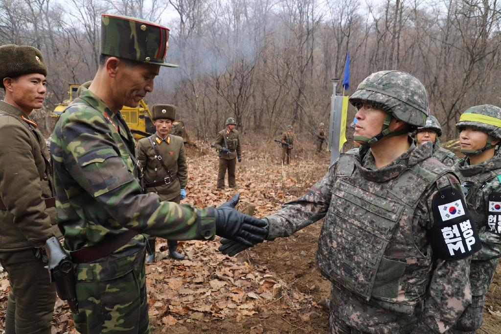 "Pictures handed out by Seoul's defence ministry Thursday showed a South Korean soldier and a North Korean counterpart taking part in the ""recent"" roadworks holding their hands out toward each other, with their colleagues watching"