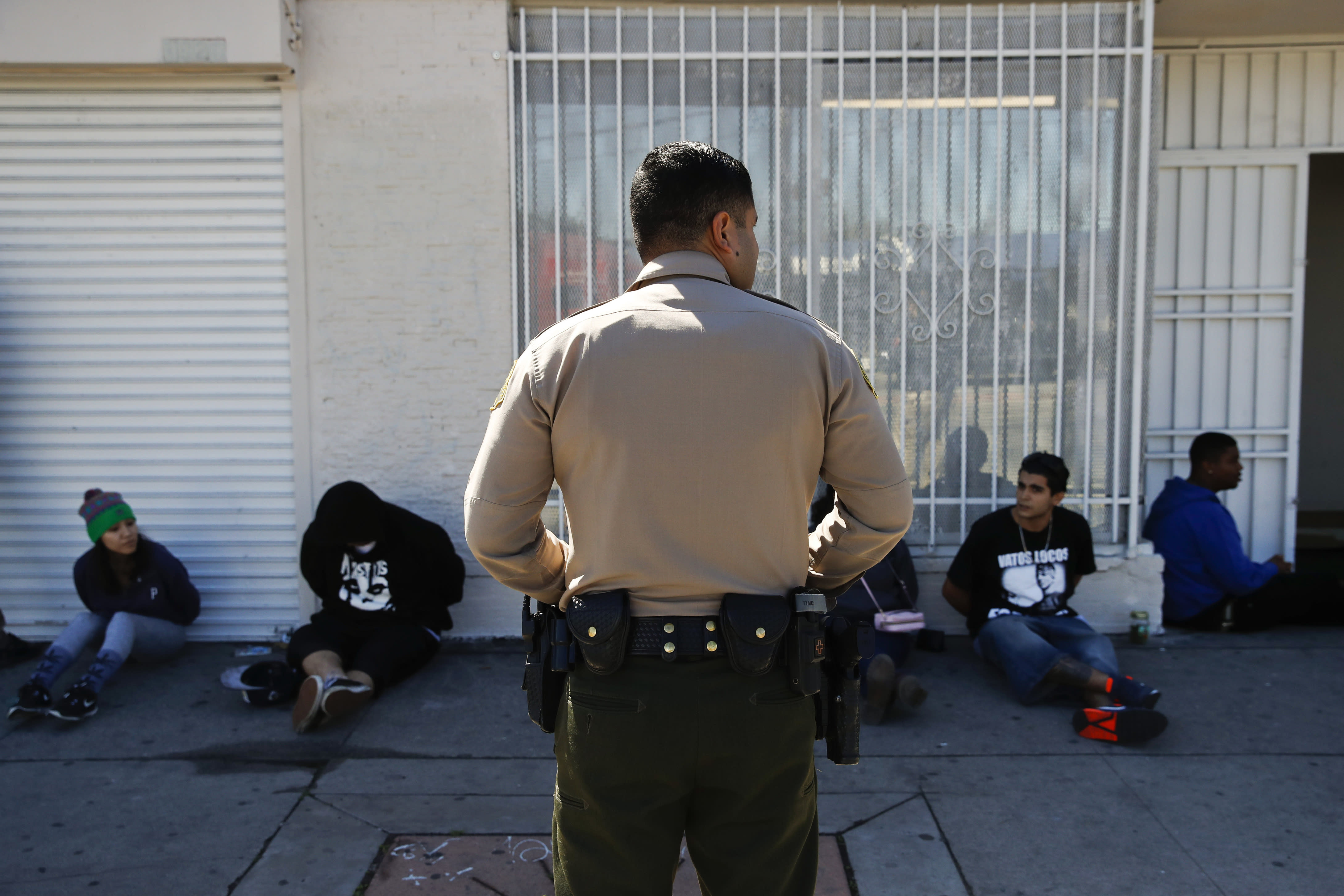 FILE - In this March 15, 2018 file photo, a Los Angeles County Sheriff's deputy keeps watch on a group of people apprehended at an illegal marijuana dispensary in Compton, Calif. The number of felony marijuana arrests in California continued to plunge in 2019 in the age of legalization, but another trend remained unchanged: those arrests fell disproportionately on Hispanics and Blacks, state data showed. (AP Photo/Jae C. Hong, File)