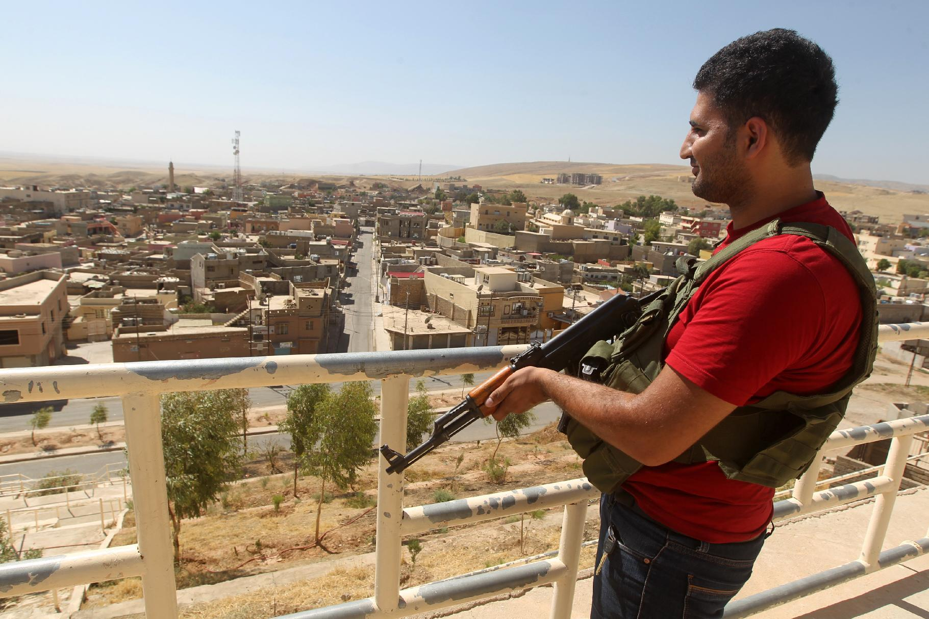 An Iraqi Yazidi fighter stands guard outside a shrine in Sheikhan, on August 10, 2014