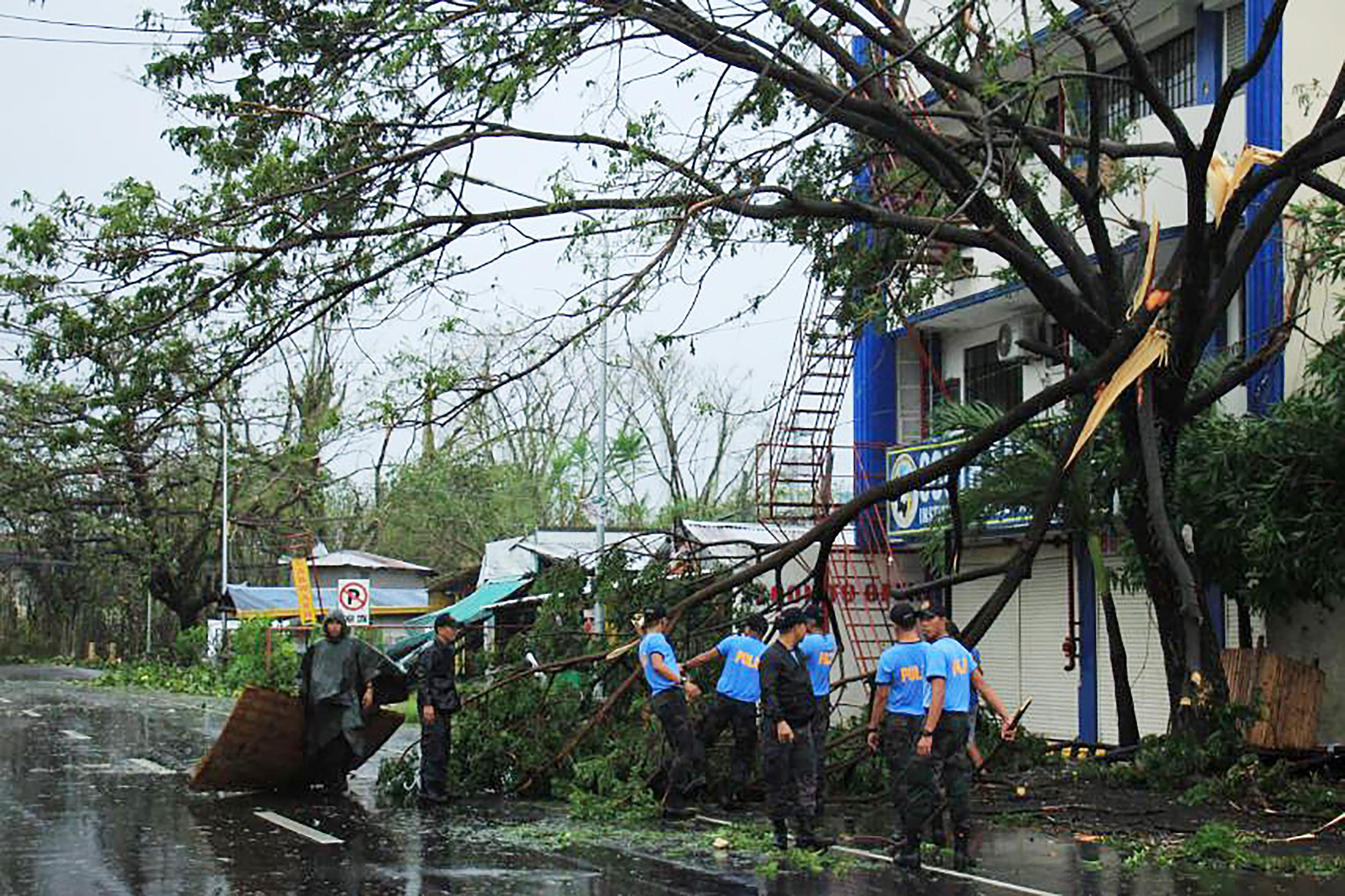 Policemen remove branches from a damaged tree following the passage of Typhoon Kammuri in Legaspi City, Albay province, south of Manila on December 3, 2019. - Typhoon Kammuri lashed the Philippines with fierce winds and heavy rain, as hundreds of thousands took refuge in shelters and the capital Manila prepared to shut down its international airport over safety concerns. (Photo by RAZVALE SAYAT / AFP) (Photo by RAZVALE SAYAT/AFP via Getty Images)