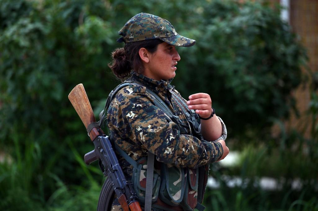 A fighter from the Kurdish female Women's Protection Units stands while carrying a rifle behind her shoulder during a training exercise (AFP Photo/DELIL SOULEIMAN)