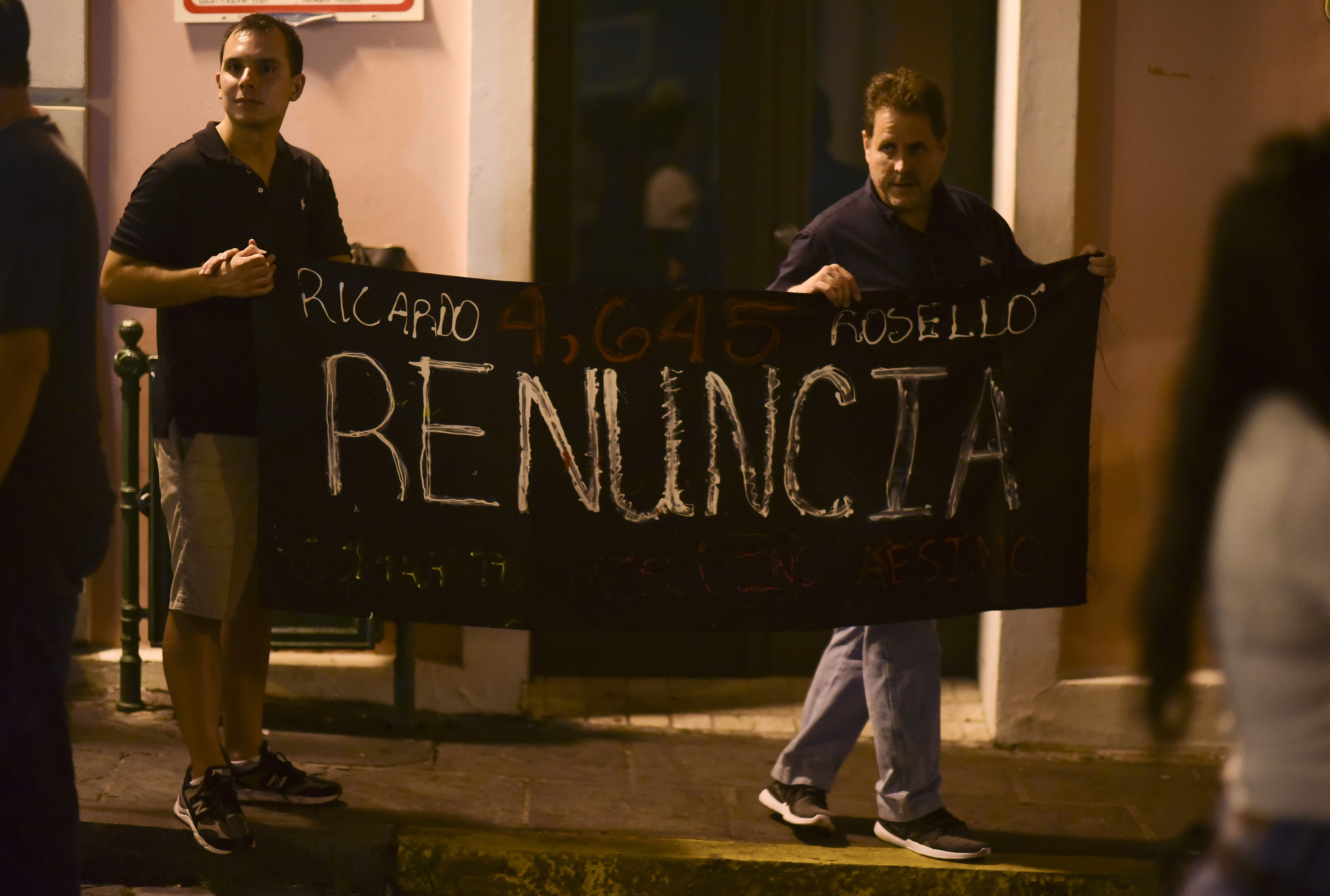 Citizens carrying a banner that reads in Spanish