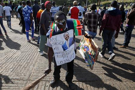 A supporter of Kenyan opposition leader Raila Odinga of the National Super Alliance (NASA) coalition carries banners and flags ahead of Odinga's planned swearing-in ceremony as the President of the People's Assembly in Nairobi