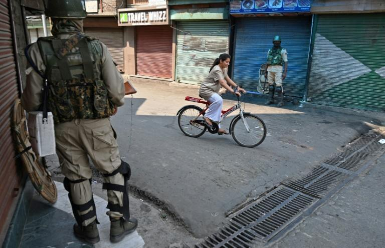 A Kashmiri girl rides past Indian paramilitary troopers in Srinagar