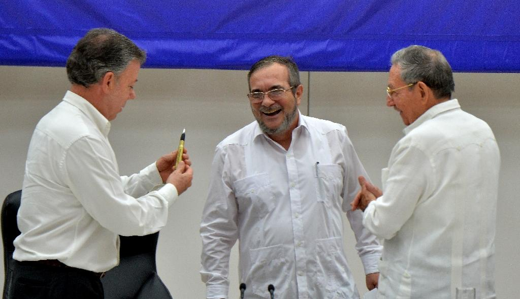 Colombian President Juan Manuel Santos (L), the head of Colombia's FARC guerilla, Timoleon Jimenez, (C) and Cuban President Raul Castro (R), during the signing of the ceasefire between the Colombian government and the FARC guerrilla on June 23, 2016 (AFP Photo/Adalberto Roque)