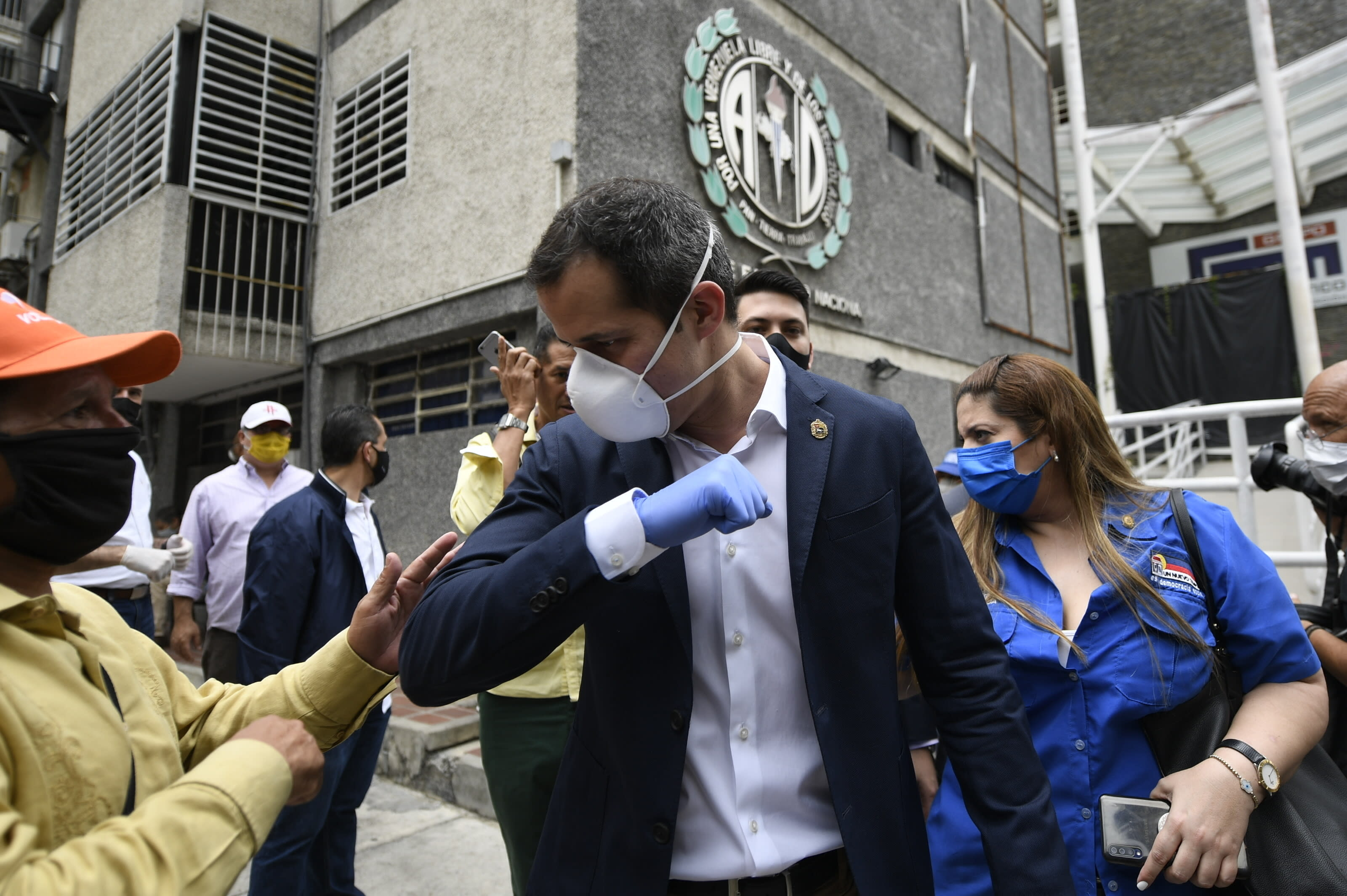 FILE - In this June 17, 2020 file photo, Venezuelan opposition leader Juan Guiado greets a supporter after a visit to the headquarters of Democratic Action political party in Caracas, Venezuela, the day after Venezuela's Supreme Court ordered its takeover ahead of parliamentary elections expected this year. More than a year after the U.S.-backed politician rose up to oust Venezuelan President Nicolás Maduro, the socialist leader holds a yet stronger grip on power, thanks partly to the novel coronavirus. (AP Photo/Matias Delacroix, File)
